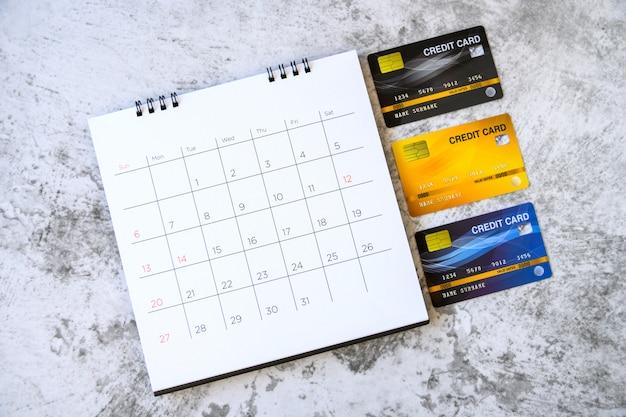 Календарь с днями и кредитные карты на столе. концепция покупок