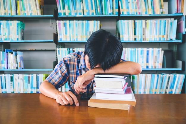 Утомленный азиатский студент спать на столе в библиотеке