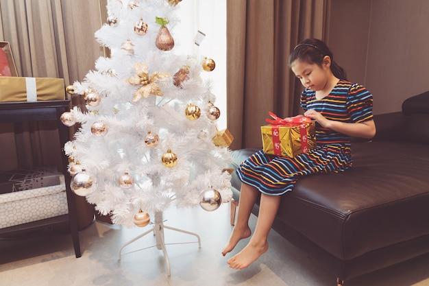 Счастливая маленькая азиатская девушка с подарочной коробкой рождества.