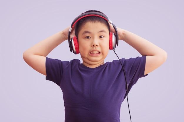 Наушники азиатского мальчика нося слушая к музыке и сумашедшие и кричащие возбужденные, изолированные на серой предпосылке