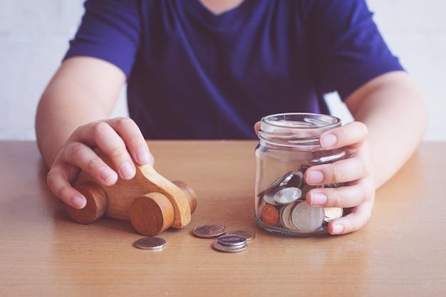車を買うためのお金を節約する少年。車のコンセプトを購入するための計画。