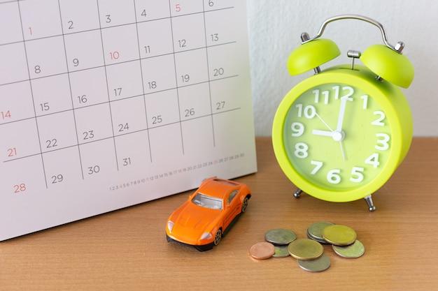 カレンダーとテーブルの上の車。車の購入または販売、レンタル、ローン、修理の支払いの日