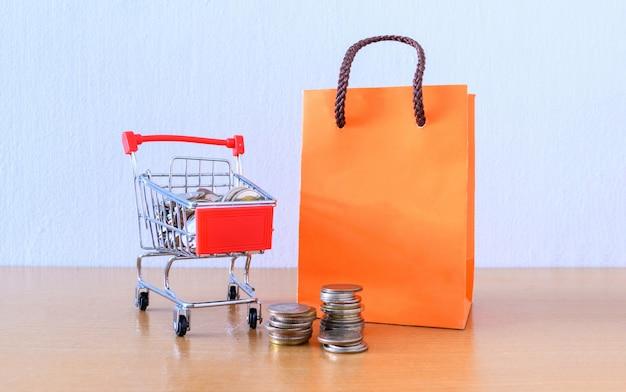 Супермаркет тележки и оранжевая бумажная сумка на деревянной таблице. концепция покупок