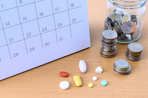 カレンダーと薬とテーブルの上のコイン。コンセプト
