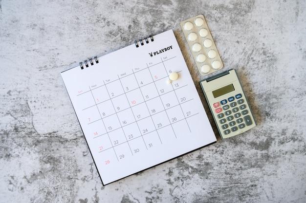 Таблетки на фоне календаря. концепция здравоохранение