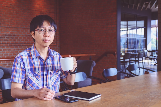 カフェでコーヒーを飲む若いアジア人