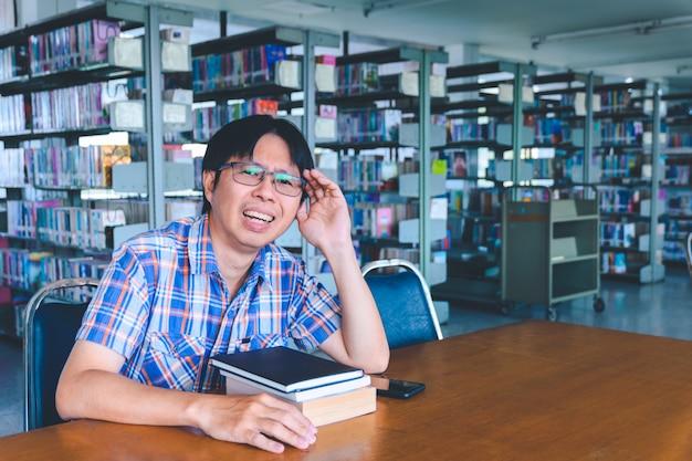 Скучающий азиатский студент с книгами в библиотеке