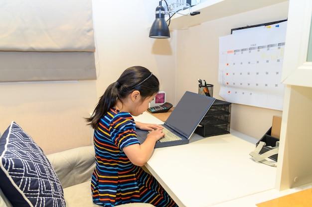 Маленькая азиатская девушка с портативным компьютером. концепция образования.