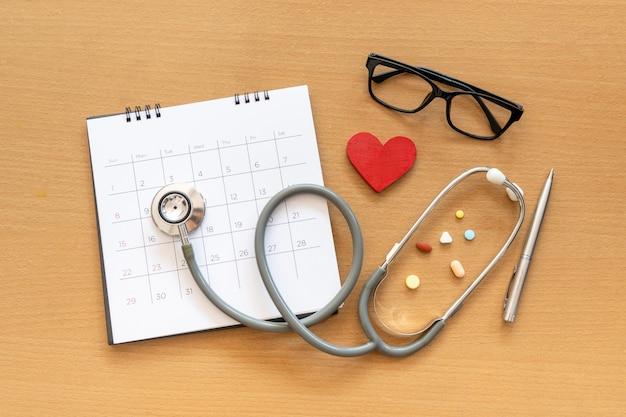 Стетоскоп и календарь на деревянном столе, график, чтобы проверить здоровую концепцию