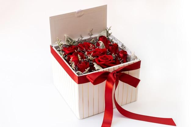 正方形の白いギフトボックスにロマンチックな赤いバラ。白い背景の上