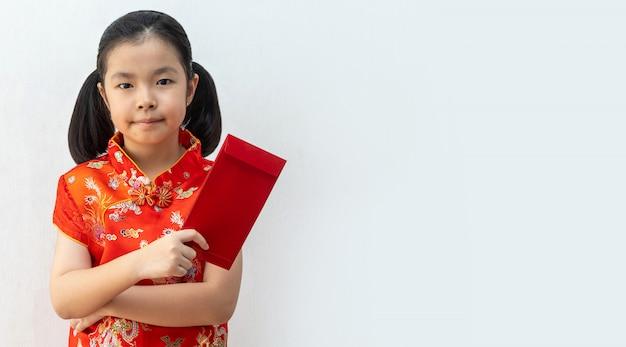 アジアの女の子はチャイナドレスを着て、中国の旧正月に赤い封筒を取る