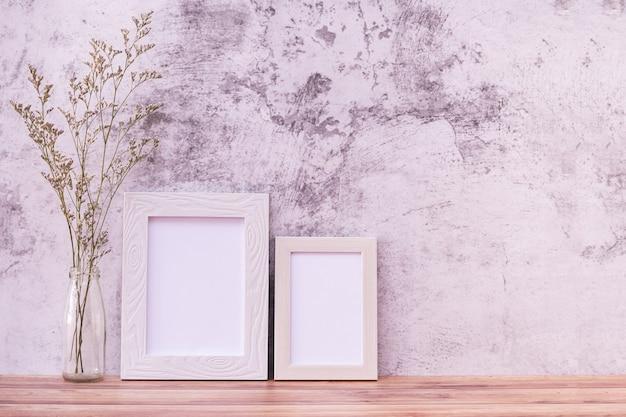 壁と木製のテーブルの上に花の額縁。