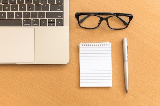 メモ帳とラップトップのオフィスの木製のテーブルの上から見るデスク