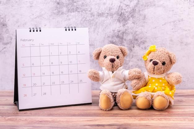テーブルの上のカレンダーとテディベアカップル