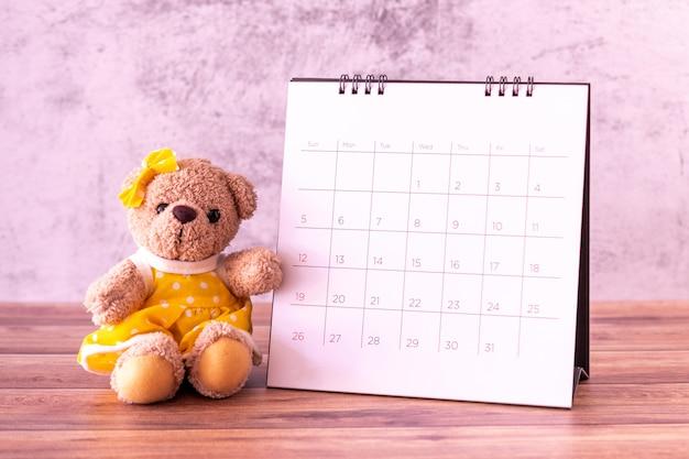 テーブルの上のカレンダーとテディベア