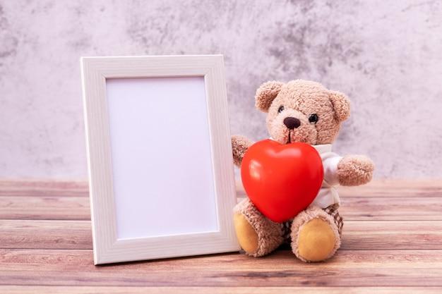Плюшевый мишка с рамкой и сердцем на столе