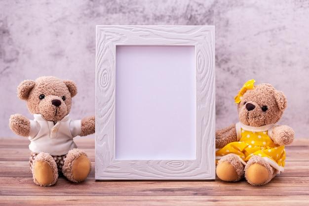 木製のテーブルの写真フレームとカップルのテディベア。