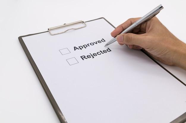 Рука человека с ручкой над документом, выберите «утверждено» или «отклонено».