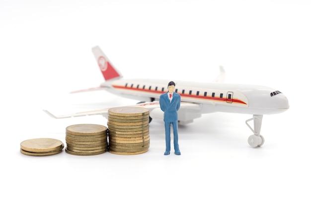 コインとその背後の飛行機に立つミニチュアビジネスマン。貯蓄とローンのコンセプト。