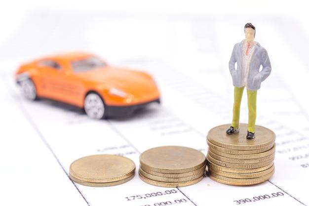 Миниатюрный бизнесмен и стек монет на заявлении и автомобиль позади. экономия и кредит.