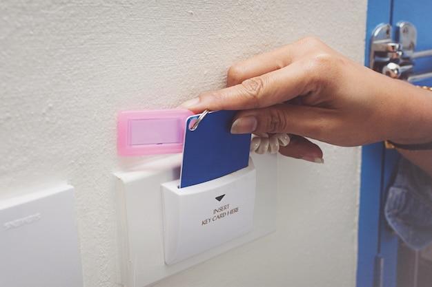 ドアのアクセス制御のためのアジアの女性の手のホールドカードは、ロックとロックを解除するキーカードをスキャン