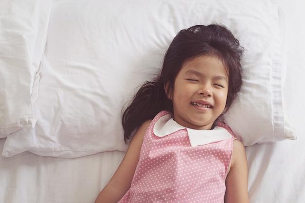 Азиатская девочка спит в постели