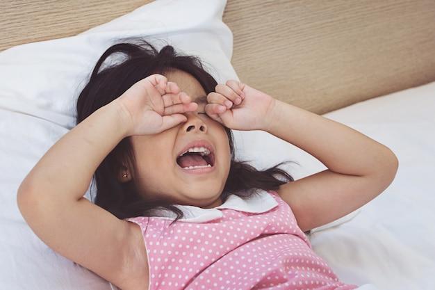 アジアの女の子、ベッドで泣いている