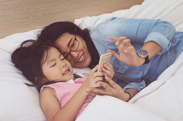 若いお母さんと彼女の小さな娘は家庭のベッドでスマートフォンを使用しています
