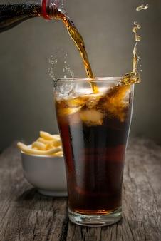 フライドポテトの背景を持つ木製のテーブルの上のグラスにコーラを注ぐ。