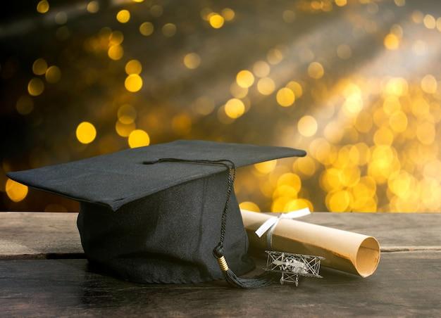卒業の帽子、木のテーブル、抽象的な明るい背景に学位論文の帽子