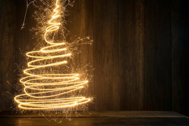 木のテーブルと木製の壁の背景を持つ花火を使用して作成されたクリスマスツリー