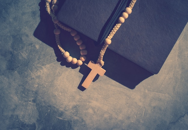 セメントテーブルの祈り、ロザリオの背景の上の古い本とカトリックロザリオビーズ