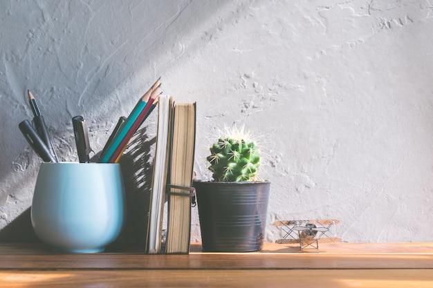 オフィスの木のテーブルモダンなインテリアの背景概念に関するノートブックとサボテンの花。