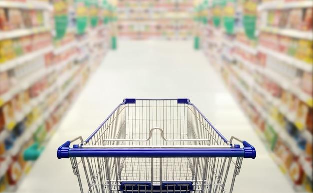 空っぽのショッピングカートショッピングコンセプトとスーパーマーケットの抽象的なぼやけた写真。