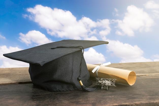 卒業の帽子、木のテーブルに学位論文の帽子