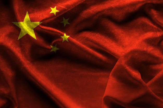 中国の背景とテクスチャの手を振っているファブリックの旗