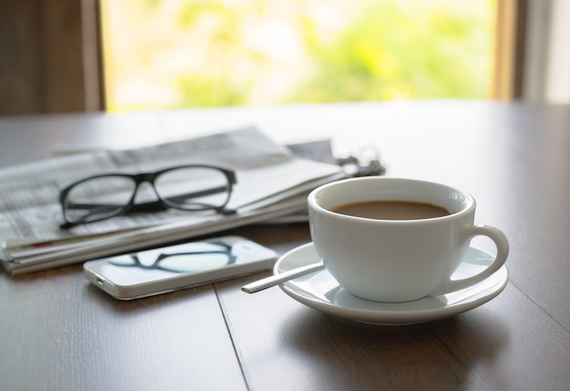 新聞読書メガネコーヒーカップとビジネスデスクビジネス新聞背景に携帯電話。