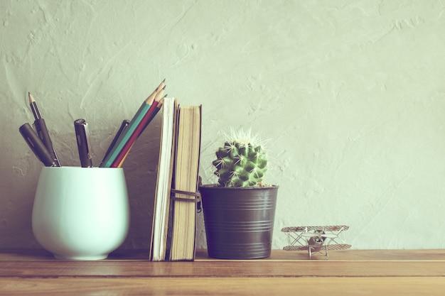 オフィス木製テーブルモダンなインテリアの背景にノートとサボテンの花。