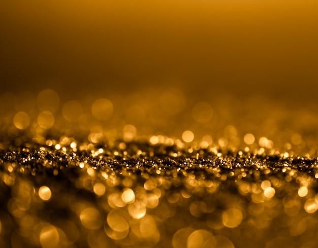 キラキラ輝きビンテージライトの背景。ダークゴールドと黒。デフォーカス。