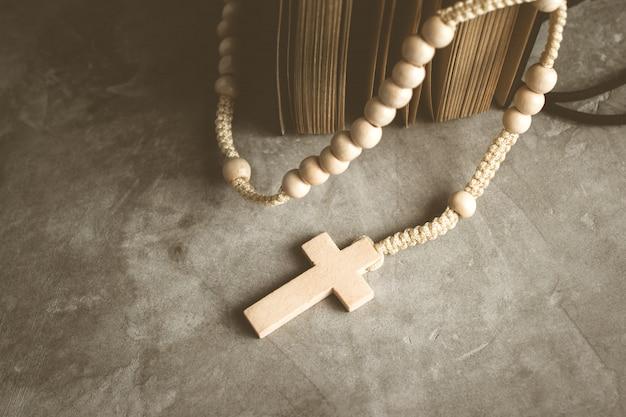 セメントテーブルの祈り、ビンテージトーンのロザリオの背景の古い本とカトリックのロザリオビーズ。