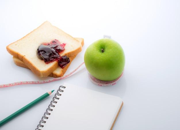 白のスライスと青リンゴの周りに巻いた測定テープ
