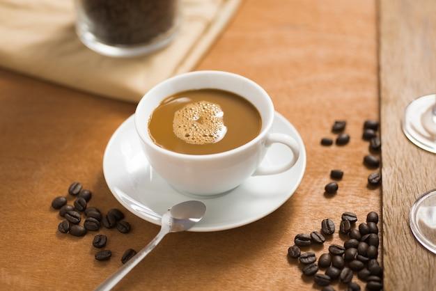 コーヒーショップの木製テーブルの上の豆とコーヒーカップ