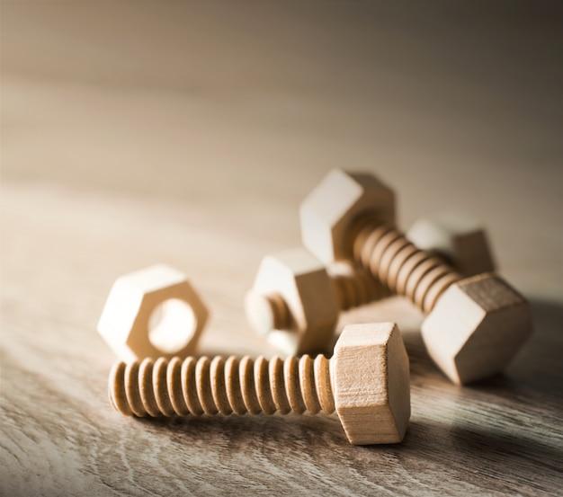 木製テーブルの上の木のナットとボルト作業の概念。