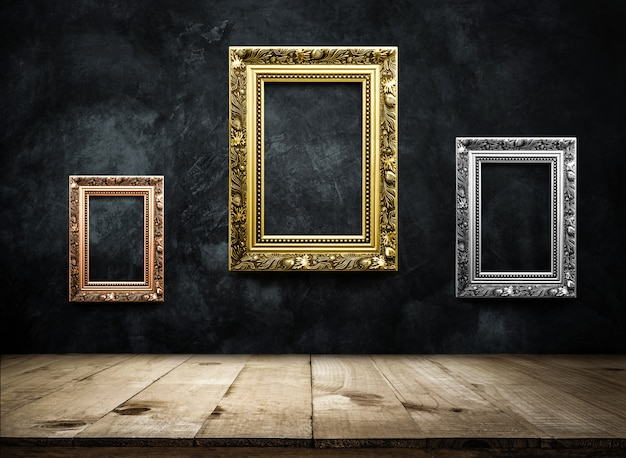 木製テーブルトップと暗いグランジ壁にアンティークの写真フレームの銅、銀、金