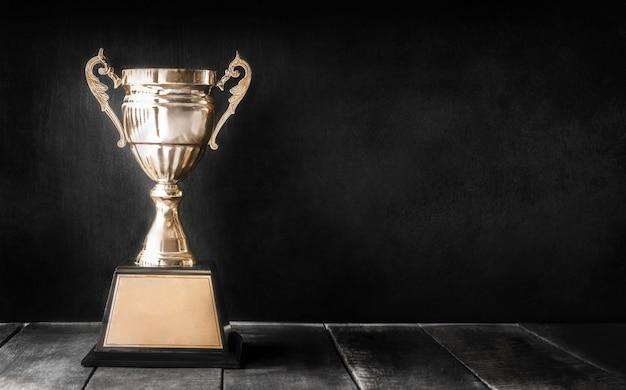 黒板コピースペースの木製テーブルの上のチャンピオンゴールデントロフィー