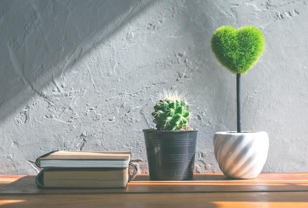 緑の心、木のテーブル、愛とバレンタインデーの概念の背景、背景に本サボテンの花。