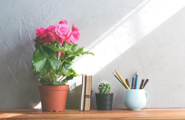 サボテンの花、オフィス木製テーブルモダンなインテリアの背景にノートとピンクの花。