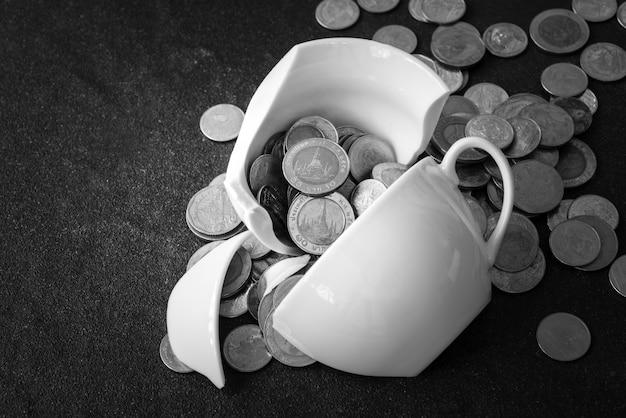 カップがバラバラになったばかりで、コインがその周りに散らばっています