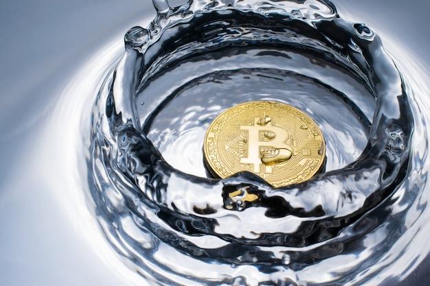 Золотая монета биткойн с фоном крипто валюты брызг воды.
