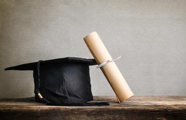 卒業キャップ、木製テーブル空の度紙付き帽子